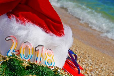 Santa Claus hat and toys оn sand on the sea background. 2018                            Standard-Bild