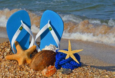Bunte Flipflops, Starfish, Kokosnuss und Seil am Strand. Standard-Bild - 90566687