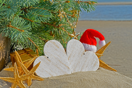Christmas decoration on sea background. The Santa Claus hat and starfish.