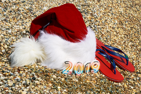 Santa Claus hat and toys оn sand on the sea background.