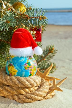 Weihnachtsdekoration auf Seehintergrund. Der Weihnachtsmann Hut auf dem Globus. Standard-Bild - 90739504