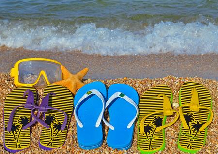 Colorful flip flops, starfish and underwater mask on the beach. Standard-Bild