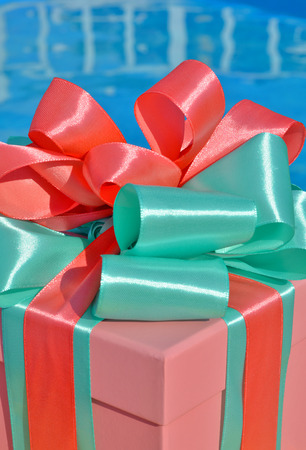 Christmas gift box against background of the blue pool. Standard-Bild