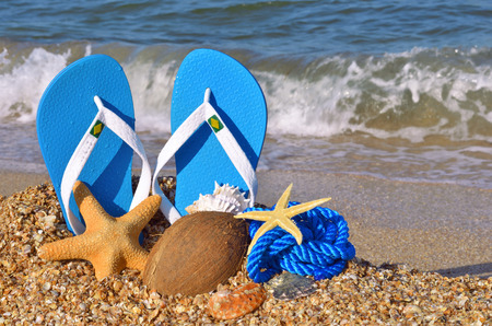 Colorful flip flops, starfish, coconut and rope on the beach. Standard-Bild