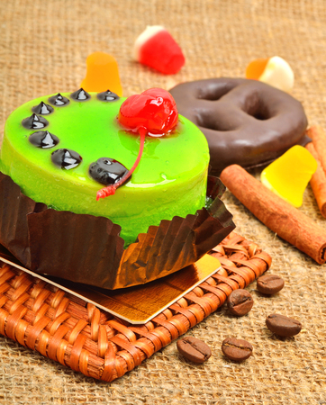 Cake in green jelly with cherry and chocolate icing on sackcloth.