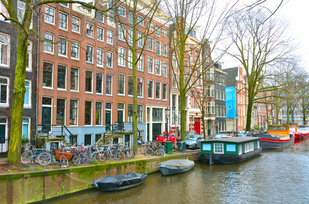 View of the canal of Amsterdam, with bicycles and pleasure boats.