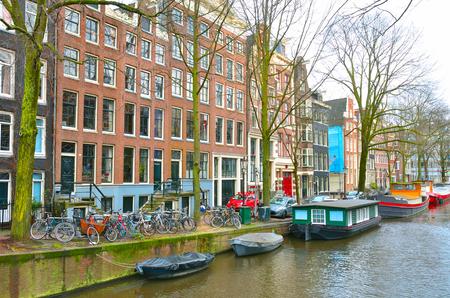 Blick auf den Kanal von Amsterdam, mit Fahrrädern und Sportbooten. Standard-Bild - 95052204