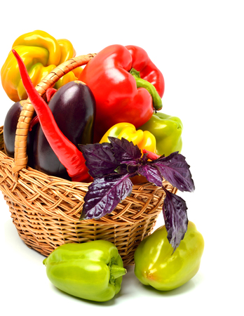 Sweet peppers, eggplant, chilli pepper and basil in the basket isolated on white background Stock Photo