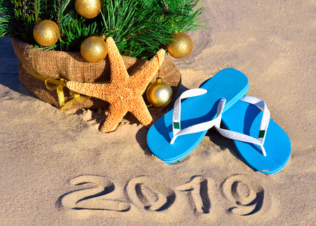 New Year 2019 on the beach. Christmas tree, starfish and slippers in sand Standard-Bild - 121736319