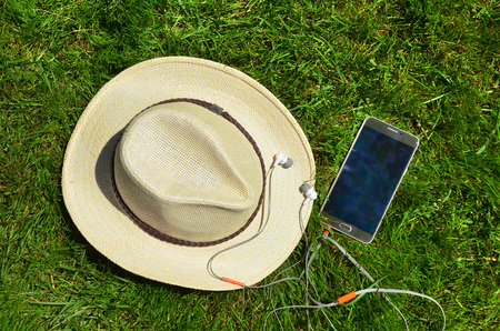 Hat with mobile phone and headphones on the green grass.