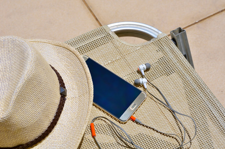 Hat with a mobile phone and headphones on a wicker chair near the pool. Standard-Bild - 121735973