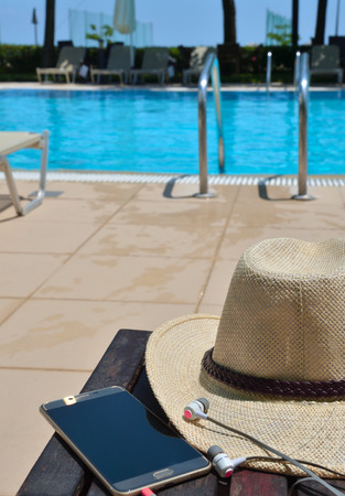 Hat with mobile phone and headphones on the green grass. Hotel in Greece. Standard-Bild - 121735976