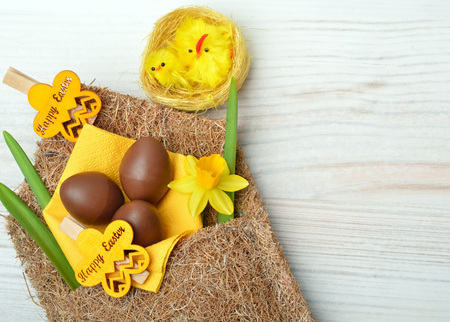 Easter decoration and fresh spring narcissus flowers on wooden background.