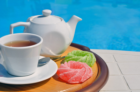 Tea in a cup with marmalade in front of the pool.