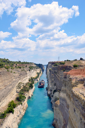 Corinth Canal in a bright sunny day against a blue sky. Among the rocks floating white yachts in turquoise water.
