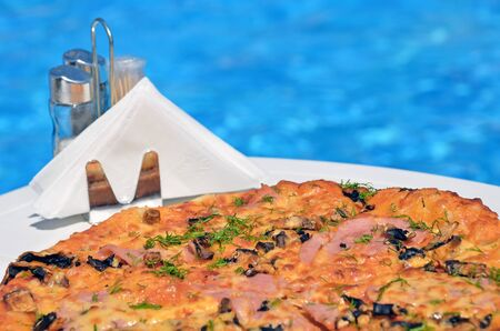 Tasty pizza on the swimming pool background Reklamní fotografie