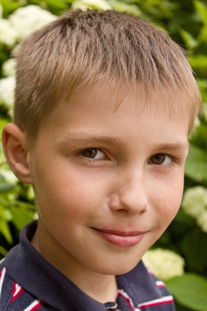 portret: Portret of little smiling boy near flowers outdoors Stock Photo