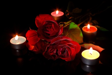 glowing candle: Red roses with candles on black