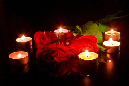 Red roses with candles on black photo