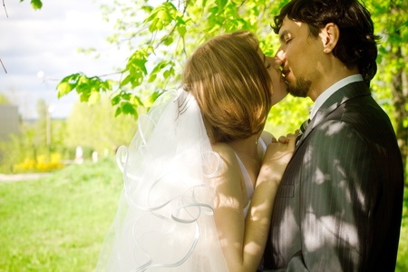 Beautiful young bride kissing with  her groom Stock Photo - 9530882