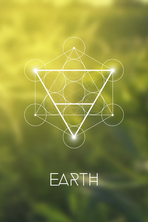 Sacred geometry Earth element symbol inside Metatron Cube and Flower of Life in front of natural green blurry background.