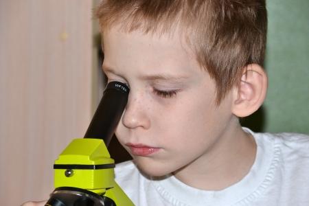 researches: L'adolescente conduce ricerche, alla ricerca in un microscopio
