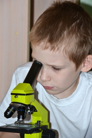 researches: The teenager conducts researches, looking in a microscope Stock Photo