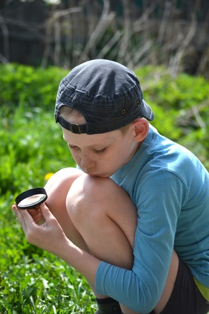 observes: the teenager observes through magnifying glass