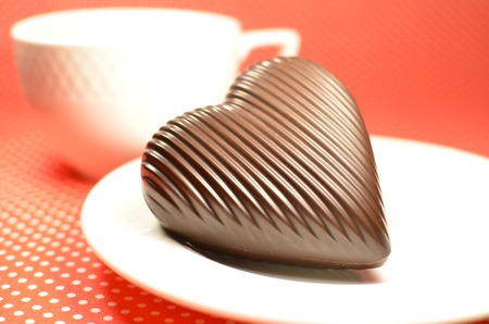 Chocolate striped heart on a white plate against a red colored tablecloth with white dots