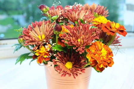 sill: Bouquet of autumn flowers on the window sill at home