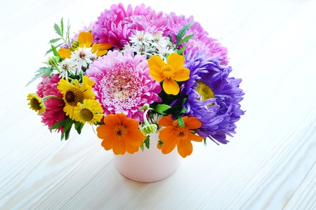 pot marigold: Multi-colored bouquet of different autumn flowers in the pot on a wooden background