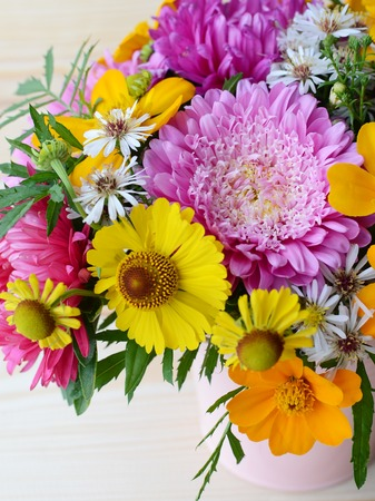 pot marigold: Multi-colored bouquet of different flowers in the pot on a wooden background