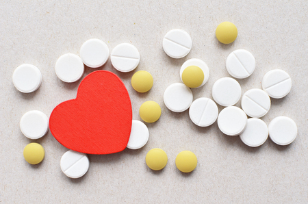 depressant: a lot of white and yellow cardio tablets on grey paper background, healthy heart concept
