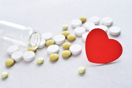 depressant: a lot of white and yellow cardio tablets with small pills bottle healthy heart concept Stock Photo