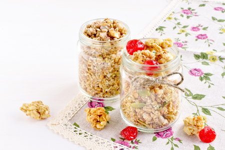 small glass jars full of crispy cherry granola snack, natural flax napkin with floral print, healthy breakfast concept