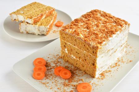zoet worteltaart dessert met room van zure room, witte houten achtergrond