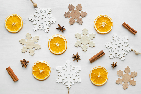 Christmas frame composition with dry oranges, cinnamon sticks, anise stars and wooden snowflakes over white wooden background. Flat lay, top view, happy holiday concept