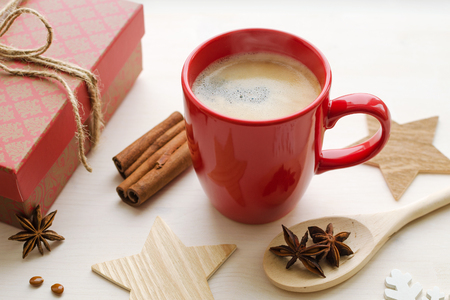 red cup with black strong espresso coffee with elevated steam, white wooden background, gift in beautiful box, anise stars, cinnamon sticks, wooden decorative elements, holiday time concept 版權商用圖片