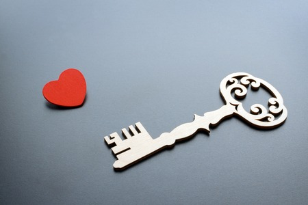 vintage key with red heart on grey background