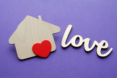 wooden house shape with red heart, family love and happy life concept Standard-Bild
