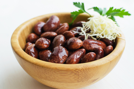 red canned beans with fresh parsley and horse-radish in wooden bowl over light background