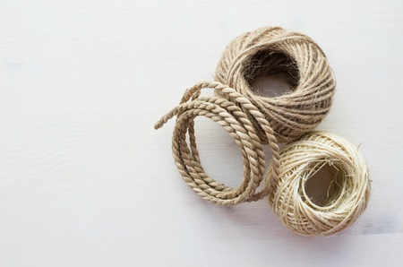 natural material different ropes over white wooden background, top view, copy space