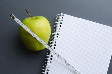 Diet plan notepad with fresh green apple and measuring tape with copy space for healthy food concept