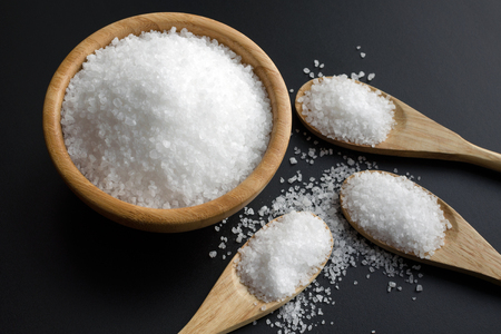 Sea Salt Crystals In Wooden Spoons and bowl over black chalk board background, healthy food concept