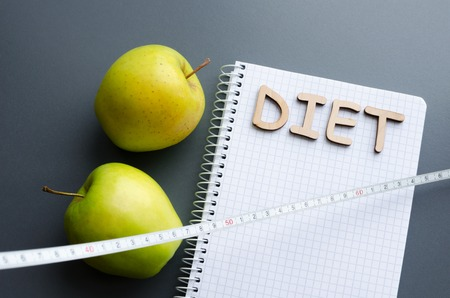 notepad with letters diet, fresh green apples and measuring tape, healthy food concept