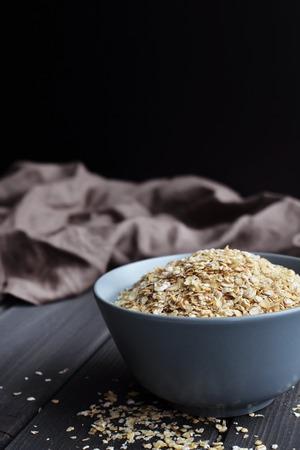 Rolled oats, healthy breakfast cereal oat flakes in bowl on dark wooden table background with texture, copy space