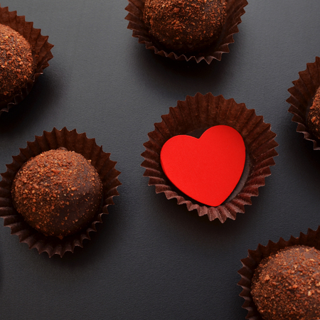 chocolate sweets in wrapper with red heart over black background, darkmood photo, top view, Saint Valentines Day card