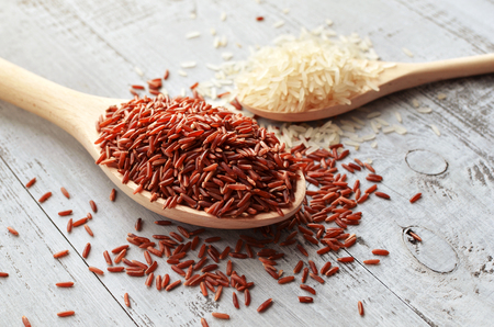 red and steamed types of rice in spoons on wooden background Stock Photo
