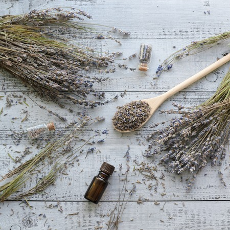 natural dry lavender flowers with organic lavender oil over wooden background
