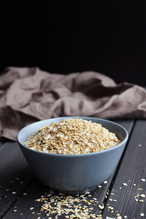 Rolled oats in ceramic bowl on dark wooden table with texture